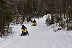 Snowmobiles riding on forest trail in the Adirondacks Royalty Free Stock Image