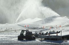 Snowmobiles under snow makers. Stock Photography