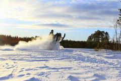 Snowmobiling i djupt pulver och hoppa arkivfoto