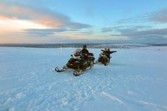Snowmobiling at sunrise sunset in Lapland, Finland stock images