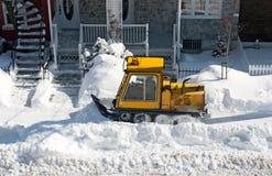 Snowplough amarelo que remove a neve na cidade imagens de stock