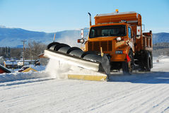 Snowplow. Big truck is plowing snow on the highway stock images