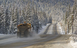 Snowplow. A snowplow scrapes snow and spreads sand on a winter highway Stock Images