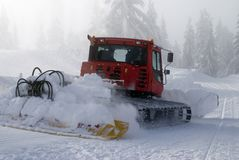 Snowplow in Action. A snowplow prepares a run at a ski resort stock images