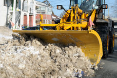 Snowplow in action. Snowplow clearing the street in a city Stock Image