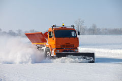 Snowplow is cleaning a road. And snow flying around it Stock Photography