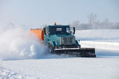Snowplow is cleaning a road. And snow flying around it Royalty Free Stock Photos
