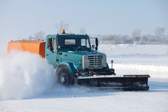 Snowplow is cleaning a road. And snow flying around it Stock Photo