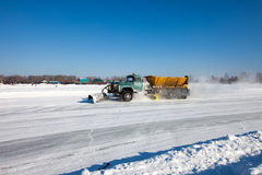 Snowplow is cleaning a road. And snow flying around it Stock Image