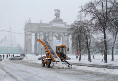 Snowplow cleans from the road snow near the entrance to VDNKh in Moscow Royalty Free Stock Photos