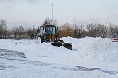 Snowplow cleans from the road snow in Victory park in Moscow. Moscow, Russia - January 15, 2016: Snowplow cleans from the road snow in Victory park in Moscow Royalty Free Stock Image