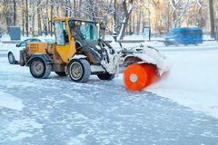 Snowplow cleans a sidewalk. In a European city Stock Photography