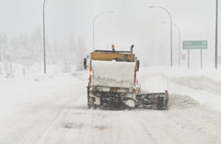 Snowplow clearing highway. A snowplow clears a snowy winter highway Royalty Free Stock Photo