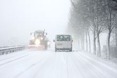 Snowplow driving in snowstorm in the Netherlands Stock Photo