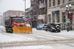 A snowplow in motion in Montreal Stock Images