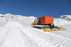 Snowplow in the mountains prepairing piste Stock Photo