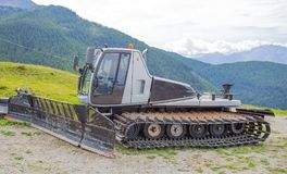 Snowplow parked in the summertime in a mountain landscape royalty free stock photos