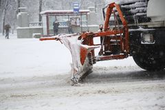 Snowplow removing snow from streets. Snowplow removing snow from city road at winter time Royalty Free Stock Photos