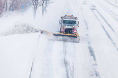 Snowplow removing the Snow from the Highway during a Snowstorm Royalty Free Stock Image