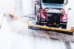 Snowplow removing the Snow from the Highway. Snowplow Truck Removing the Snow from the Highway during a Cold Snowstorm Winter Day Stock Images