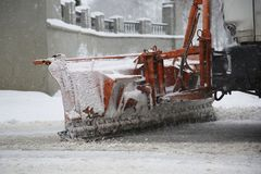 Snowplow removing snow from streets. Snowplow removing snow from city road at winter time Royalty Free Stock Photography