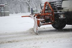 Snowplow removing snow from streets. Snowplow removing snow from city road at winter time Royalty Free Stock Image