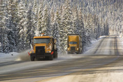 Snowplow and Semi. A semi truck follows a snowplow on a winter highway Stock Photography