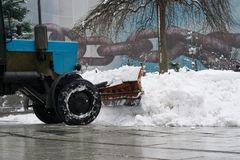 Snowplow snow removal machine clean snow. On urban streets at winter Royalty Free Stock Photo