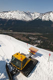 Snowplow on snowy mountain. Aerial view of yellow snowplow on snowy mountain with Seven Glaciers range in background, Girdwood resort, Alaska stock images