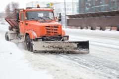 Snowplow on street. Snowplow cleans the road and sprinkles with sand Royalty Free Stock Image