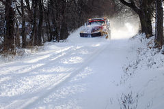 Snowplow Truck. A snowplow truck removing snow from a tree lined rural road on a cold winter day Royalty Free Stock Image