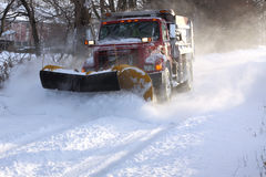 Snowplow Truck. A snowplow truck removing snow from a tree lined rural road on a cold winter day Royalty Free Stock Photos