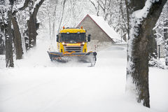 Snowplow Truck Removing the Snow from the village road Stock Photo