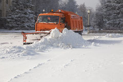 Snowplow at work. Snowplow removing snow from city road Royalty Free Stock Images