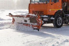Snowplow at work. Snowplow removing snow from city road Stock Images