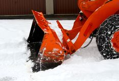 Snowplow at work to clear the road from the snow. Orange Snowplow at work to clear the road from the snow Royalty Free Stock Images