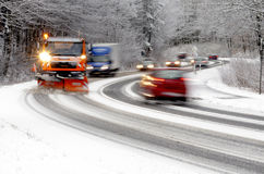 Snowplow working on winter road. Traffic on winter road with snowplow, cars blurred Stock Images
