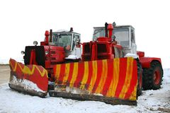 Snowplows. Two large snowplows with blades parked side by side ready to clear winter snow off the road Royalty Free Stock Photography