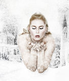 Snowqueen is blowing snowflakes Stock Photography