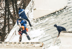 Snowremovers on rooftop Royalty Free Stock Photo
