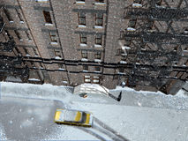 Snows on New York. Into Manhattan, a yellow cab  stopped in a street covered with snow near the door of a building, while it continues to snow Royalty Free Stock Photography