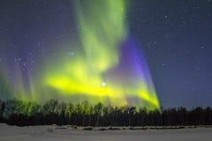 Северные света (северное сияние) над snowscape. Стоковое фото RF