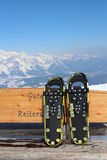 Snowshoe on bench. With Alps Royalty Free Stock Images