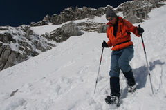 Snowshoe descent. Young woman snowshoeing in the mountains Stock Photos