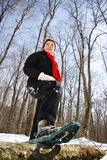 Snowshoe hiking. Woman winter hiking with snowshoes in a forest in Quebec, Canada Stock Photography