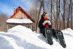 Snowshoe hiking in winter. Snowshoeing in winter. Woman on snowshoes resting from hiking in beautiful winter forest. Cabin in the background. From Quebec, Canada Royalty Free Stock Photos