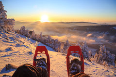 Snowshoe sunset. Winter sport activity concept. Hiker looking over his snowshoes at the beautiful landscape in the French mountains during sunset Royalty Free Stock Images