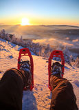 Snowshoe sunset. Winter sport activity. Male hiker looking over his snowshoes at the beautiful landscape in the French Vercors mountains during sunset Royalty Free Stock Image