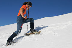 Snowshoe trip. Young woman snowshoeing. White slope and blue sky Royalty Free Stock Photography
