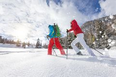 Snowshoe walkers running in powder snow with beautiful sunrise light. stock photo